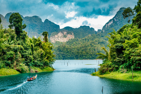 Mountain scenery with with tropical rain forest in the background and blue water lake in the foreground during a sunny day at Ratchaprapha Dam at Khao Sok National Park, Surat Thani Province, Thailand Foto de archivo