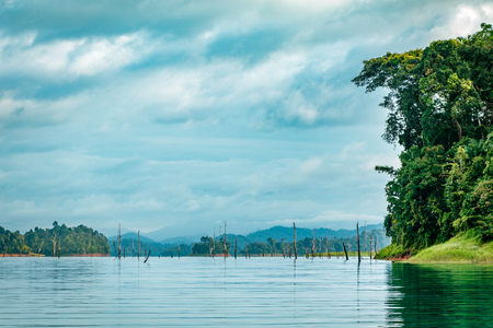 Mountain scenery with with tropical rain forest in the background and blue water lake in the foreground during a sunny day at Ratchaprapha Dam at Khao Sok National Park, Surat Thani Province, Thailand Stock Photo