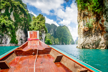 Wooden Thai traditional long-tail boat on a lake with mountains and rain forest in the background during a sunny day at Ratchaprapha Dam at Khao Sok National Park, Surat Thani Province, Thailand