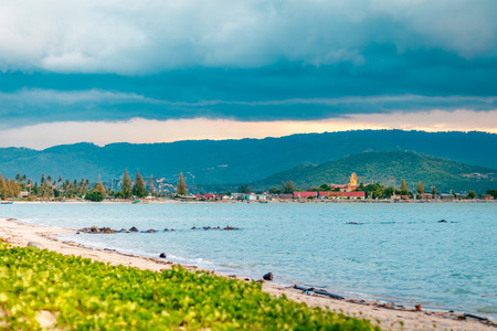 View of Big Buddha temple in the background and sandy beach with ocean in the foreground during sunset in Koh Samui, Surat Thani, Thailand