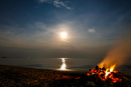 Long exposure of a full moon with bonfire on a sandy beach and ocean in the background, Khanom Beach, Thailand Stock Photo