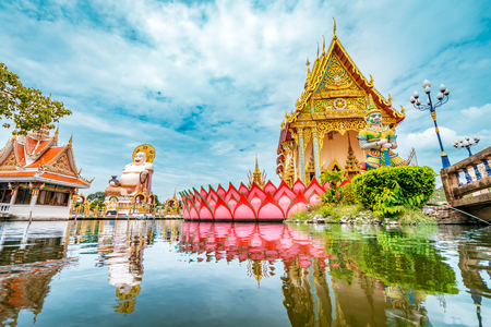 Wat Plai Laem Buddhism Temple statues during a bright sunny day with lake in the foreground in Koh Samui, Surat Thani, Thailand