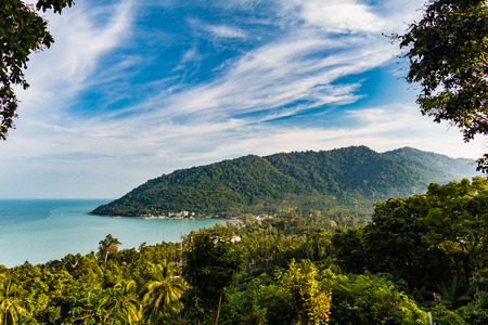 View of a tropical sandy bay during a sunny day with rain forest jungle on the left side and mountain in the background, Khanom Beach, Thailand