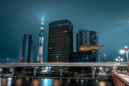 View of Tokyo Skytree tower and nearby business buildings with river in the foreground during night, Tokyo, Japan Imagens