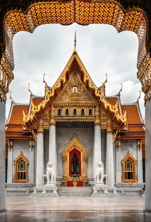 Wat Benchamabophit temple in background with golden arch in the foreground, Bangkok, Thailand