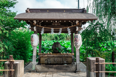 Traditional Japanese stone wash basin in Ueno Park with surrounded by trees, Tokyo, Japan Editorial