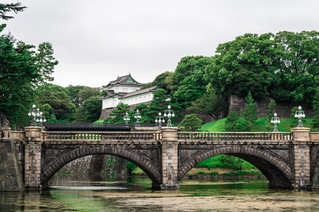 View of Edo Castle in the Imperial Palace complex with river and bridges in the foreground and trees and castle in the background, Tokyo Japan