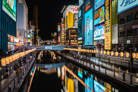 OSAKA, JAPAN - AUGUST 3, 2018: Long exposure of Famous Dotonbori shopping street of Osaka with river in the foreground and neon signs and billboards in the background during night Editorial