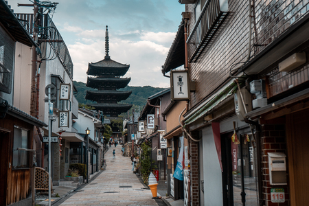 KYOTO, JAPAN - AUGUST 2, 2018: Traditional Japanese shops along a stone paved road with the Hokanji Temple in the background