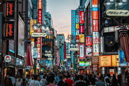 TOKYO, JAPAN - AUGUST 5, 2018: View of Shibuya shopping street with thousands of people and neon signs during sunset