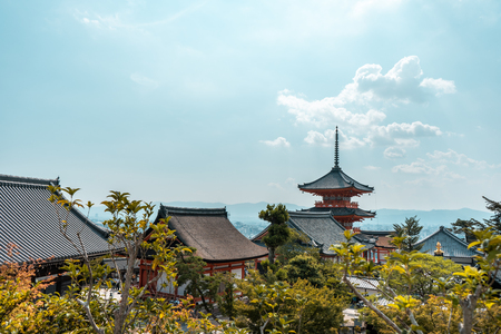 Traditional Japanese pagoda with trees in the foreground and view of Kyoto in the background in Kiyomizu-dera Temple complex, Kyoto, Japan