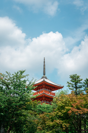 Traditional Japanese pagoda with trees in the foreground in Kiyomizu-dera Temple complex, Kyoto, Japan