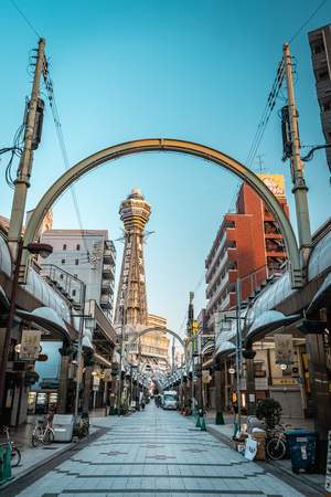 OSAKA, JAPAN - AUGUST 3, 2018: Osaka Tsutenkaku Tower with road full of shops leading towards it, Osaka, Japan Editorial