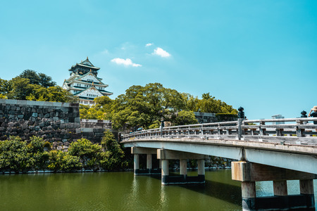 View of Osaka Castle with trees in the background and river with bridge in the foreground during a bright sunny day with blue sky, Osaka, Japan