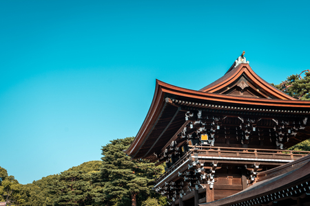 Meiji Jingu Shrine wooden entrance gate tower with trees in background during sunny day with blue sky, Tokyo, Japan Editorial