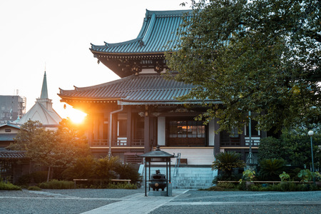 Traditional Japanese wooden pagoda during sunset with sun setting behind the temple, Tokyo, Japan Editorial
