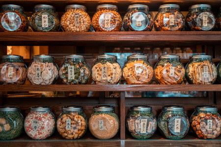 Closeup shot of nicely arranged jars on a wooden shelf filled with traditional Japanese biscuits and candies, Tokyo, Japan Editorial