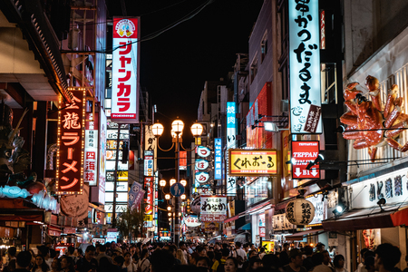 OSAKA, JAPAN - AUGUST 3, 2018: Famous Dotonbori shopping street of Osaka with thousands of people and neon signs everywhere during night