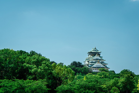 View of Osaka Castle with trees in the foreground during a bright sunny day with blue sky, Osaka, Japan Editorial