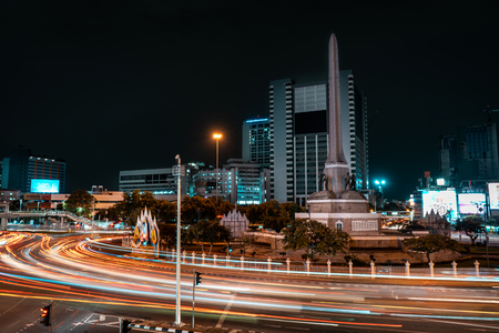 BANGKOK, THAILAND - AUGUST 17, 2018: Long exposure of the Victory Monument in Bangkok with car trails and traffic lights in foreground and buildings in background during night