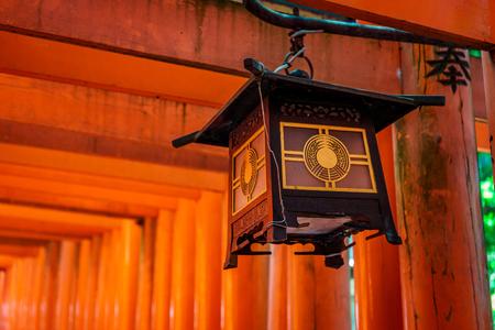 Traditional Japanese wooden lantern on a red Torii pillar in Fushimi Inari-taisha Shrine, Kyoto, Japan
