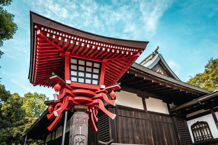 Traditional Japanese red wooden lantern with historic Japanese temple in Ueno Park during bright sunny day, Tokyo, Japan Editorial