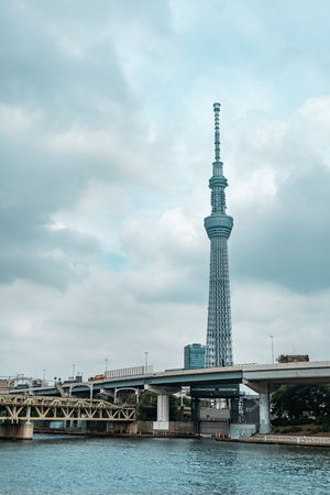 View of Tokyo Skytree tower and nearby business buildings with river in the foreground during blue overcast day, Tokyo, Japan