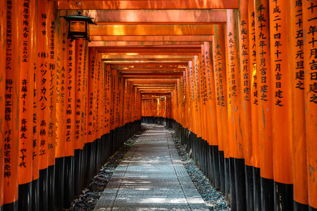 Japanese red Torii gates with black writings in Fushimi Inari-taisha Shrine, Kyoto, Japan