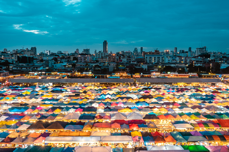 BANGKOK, THAILAND - AUGUST 12, 2018: View of the famous Train Market in Bangkok from a nearby tower during sunset with market stalls in the foreground and cityscape in the background