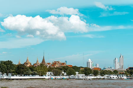 View of Bangkok skyline with the Grand Palace in background and Chao Phraya River in the foreground during bright sunny day, Bangkok, Thailand