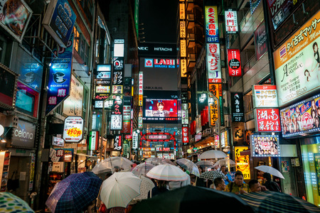 TOKYO, JAPAN - AUGUST 7, 2018: Shinjuku shopping street with thousands of people and neon signs during rainy night Editorial