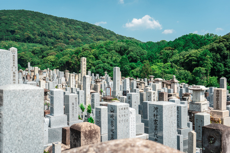 Traditional Japanese cemetery with hundreds of stone pillars with forest in the background, Kyoto, Japan Editorial