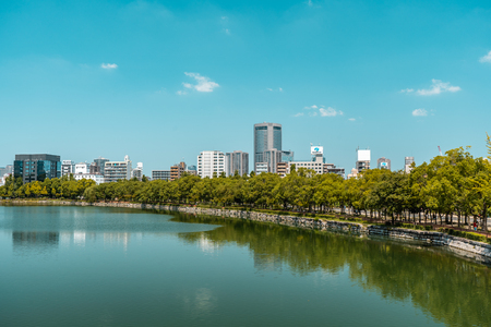 OSAKA, JAPAN - AUGUST 4, 2018: Viev of Osaka city with park and river in the foreground and office buildings in the background during a bright sunny day