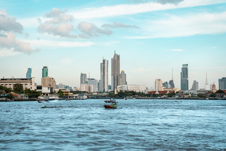 View of Bangkok skyline with the skyscrapers in background and Chao Phraya River in the foreground during bright sunny day, Bangkok, Thailand