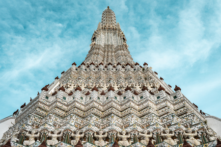 Closeup shot of stone warrior statues of Wat Arun temple during bright sunny day with blue sky, Bangkok Thailand