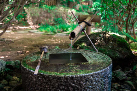 Ancient Zen stone wash basin with Japanese writings and water coming out of bamboo pipe in Ryoanji Temple, Kyoto, Japan Imagens