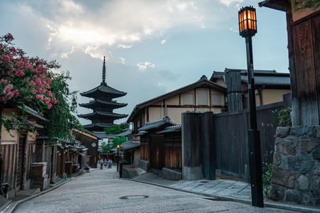 KYOTO, JAPAN - AUGUST 2, 2018: Traditional Japenese wooden houses along a stone paved road with the Hokanji Temple in the background, Kyoto, Japan