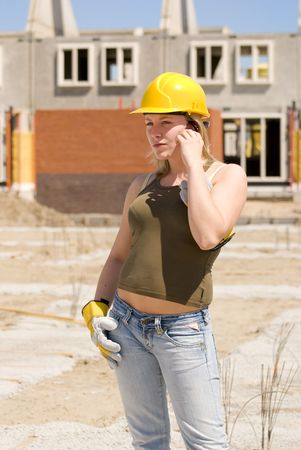 buildingsite: Young female builder with cell phone Stock Photo
