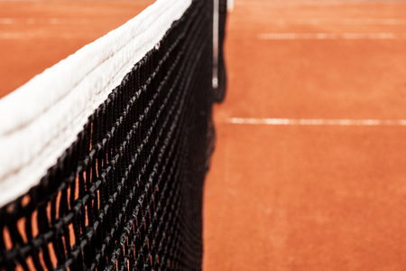Stretched mesh limiter tennis ball on a background of red tennis court Stock Photo
