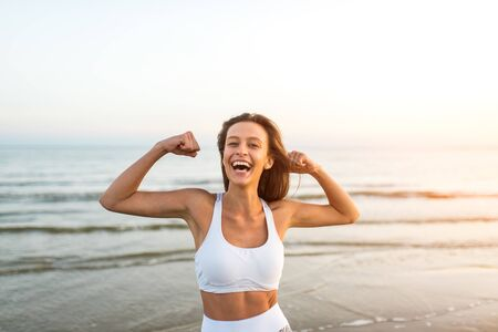 Happy carefree sportly woman enjoying beautiful sunset on the beach Stock fotó