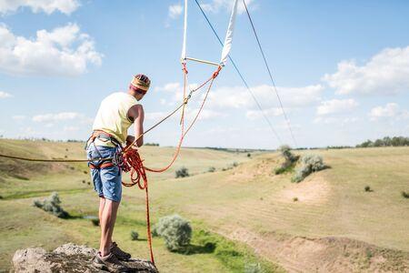 Rock climber checks insurance before use