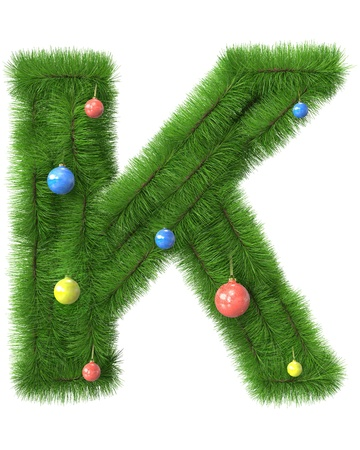 K letter made of christmas tree branches isolated on white background photo