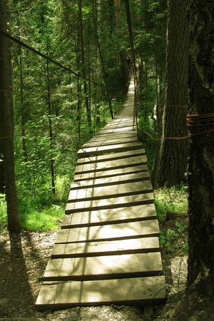 Long wooden suspension bridge in the forest. Crossing the ravine. Nobody. Ennobling the route