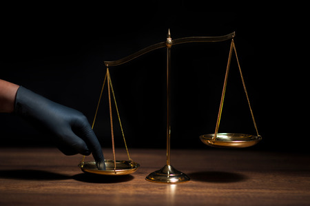 Hand with black glove pushing on scale of justice in dark room with black background. Concept of injustice, espionage, partiality, law. Stock Photo