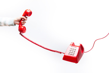 Woman holding the red phone, urgent call waiting , classic red telephone receiver in hand, old telephone isolated on white background flying in weightlessness. Stock Photo