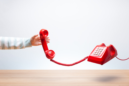 Woman reaching the red phone, urgent call waiting , classic red telephone receiver in hand, Vintage telephone on white background, flying in weightlessness with wooden desktop. Stock Photo