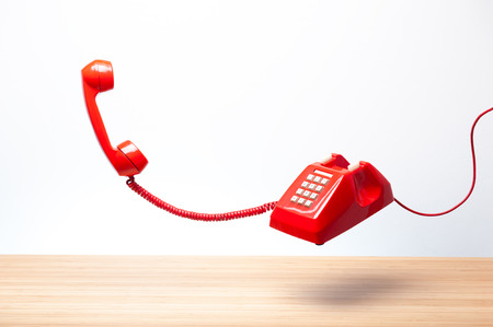 Urgent call waiting , classic red telephone receiver, old telephone on white background, flying in weightlessness with wooden desktop. Stock Photo