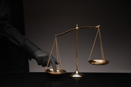 Man wearing black shirt pressing the imbalance scale on black glass desktop and black background, cheating  in a lawyers office, Concept of injustice, espionage, partiality, law.