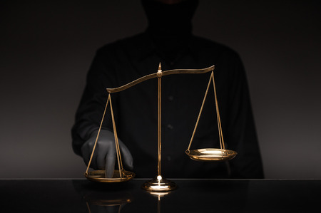 Someone wearing black shirt pressing the imbalance scale on black glass desktop and black background, cheating  in a lawyers office, Concept of injustice, espionage, partiality, law.