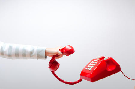 Hand holding telephone, arm wearing green and white sweater, classic red telephone receiver, old telephone on white background flying in weightlessness. Stock Photo
